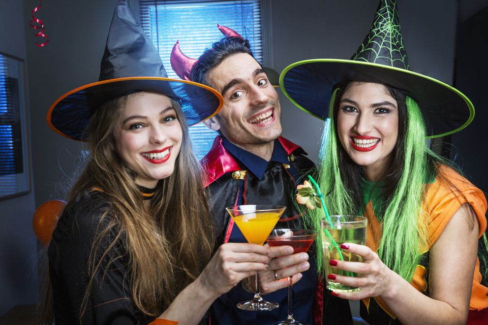 Friends dressed in halloween costumes toasting .