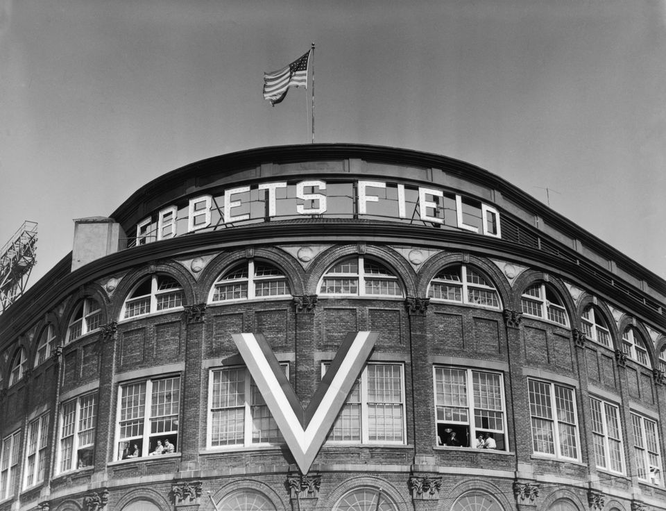 View of the curved exterior Rotunda at the entrance to Ebbets Field, home of the Brooklyn Dodgers, in the Flatbush section of Brooklyn, New York City. A 'V' for Victory, hangs on the facade.