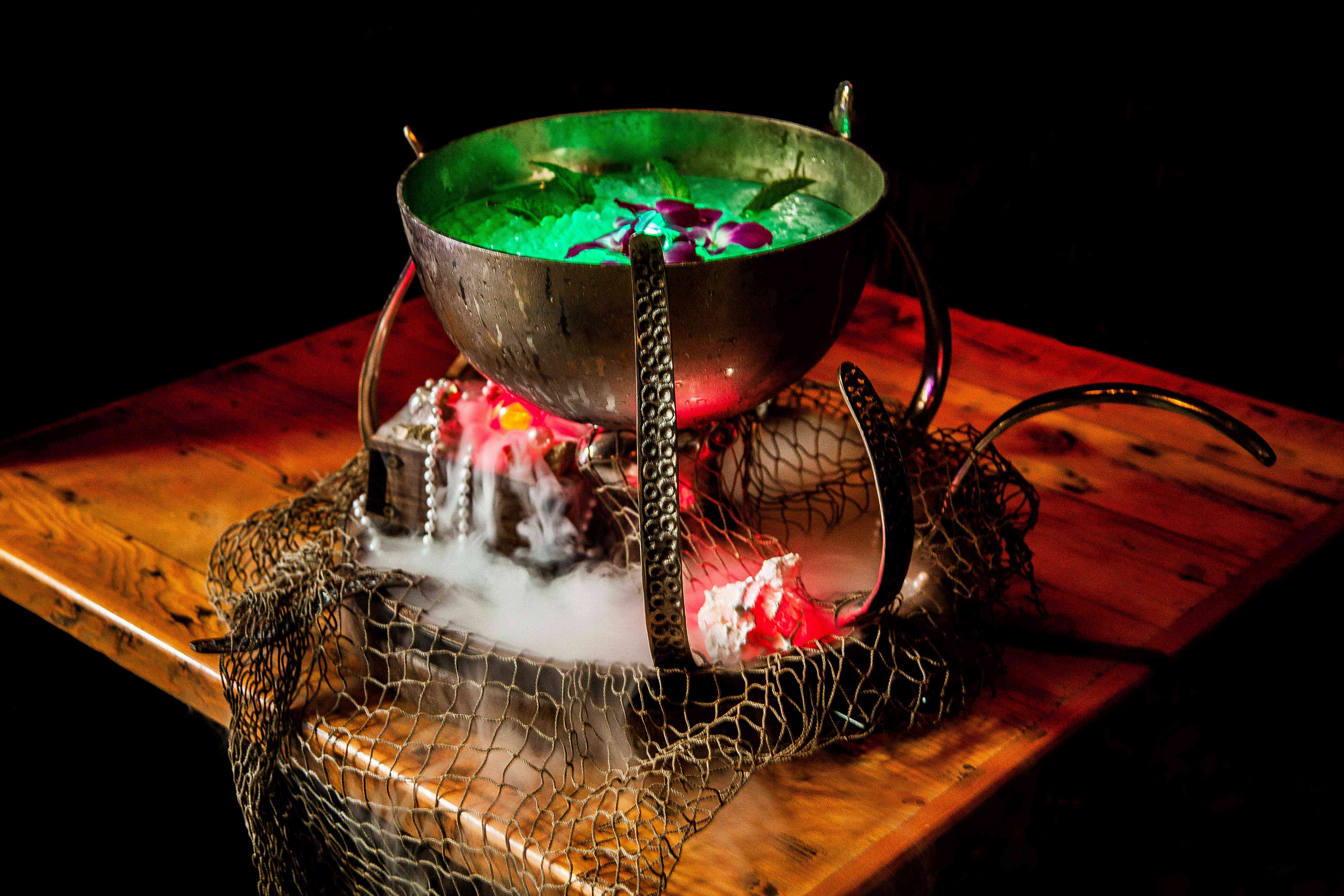 Cauldron filled with ice and a green drink with smoke coming from underneath it