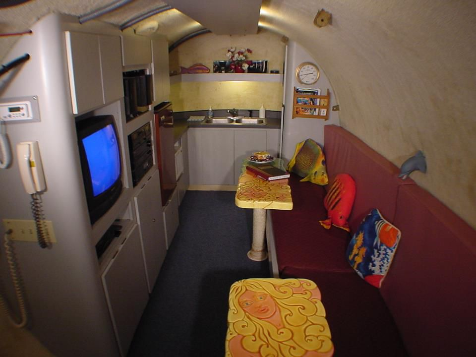 The dark underwater cabin at Jules' Undersea Lodge, with a couch, television, a kitchen, and some fish-shaped pillows
