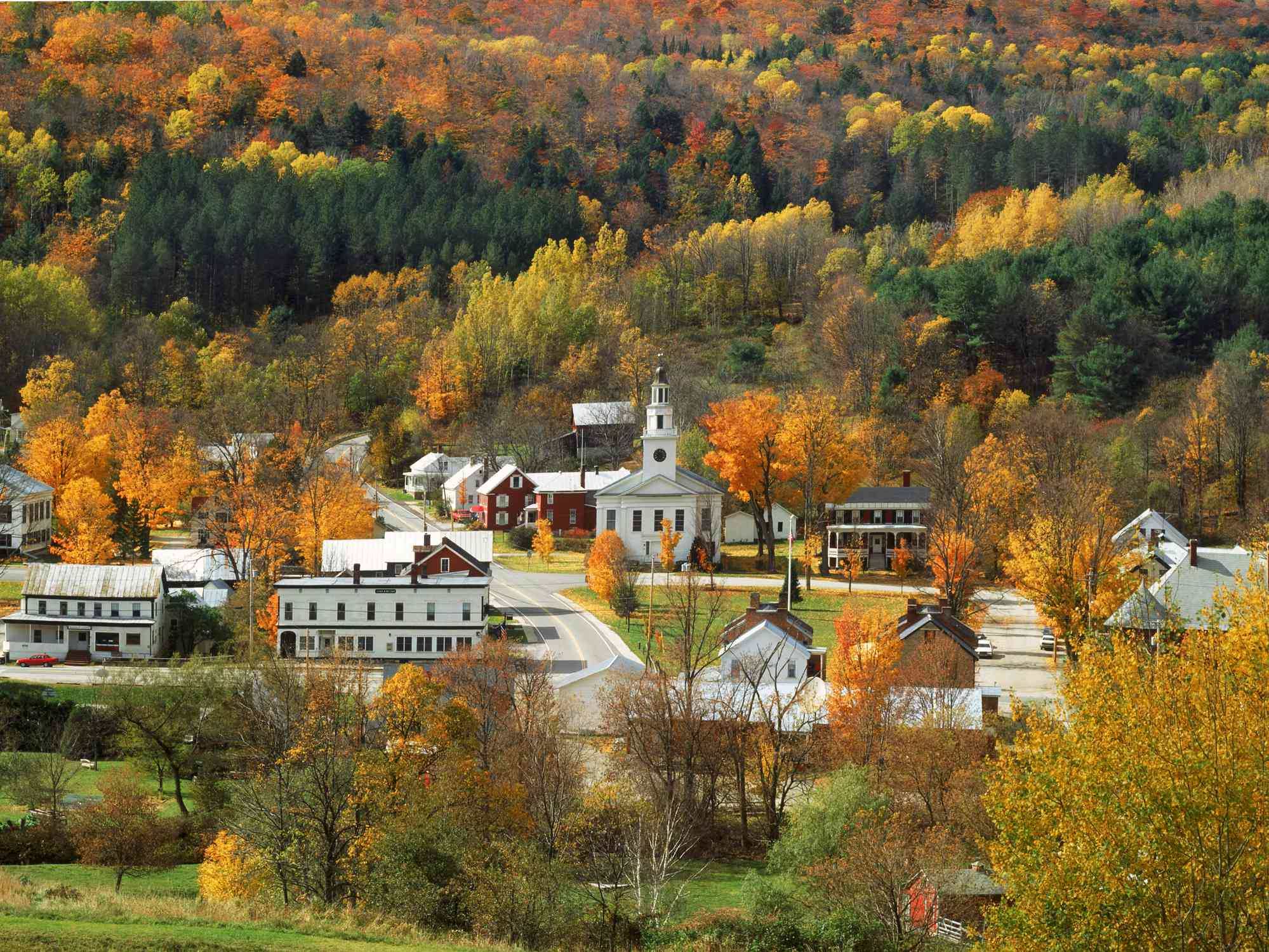 Red and white buildings in the town of Chelsea, Vermont surrounded by fall foliage