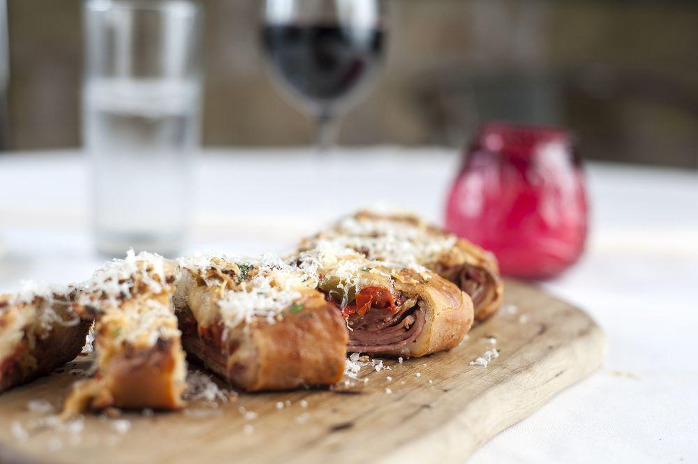 Pan enrollado con carne adentro en una tabla de cortar en Botticelli's en Austin