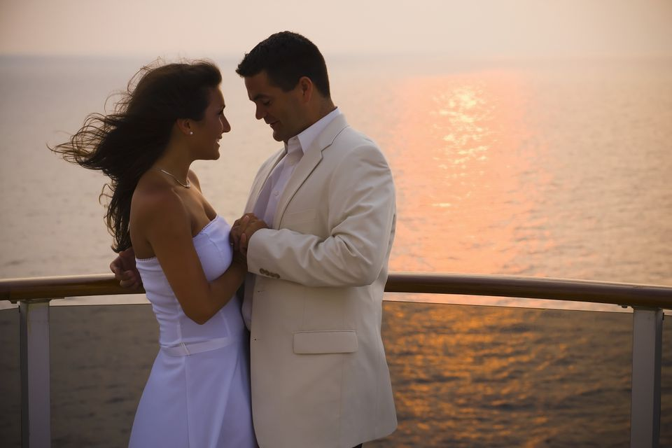 Bride and groom holding hands on cruise ship deck, sunset, side view
