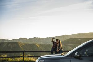 Man kissing a woman while taking a selfie. They are sitting on a low fence on the side of the road with a park car in front of them