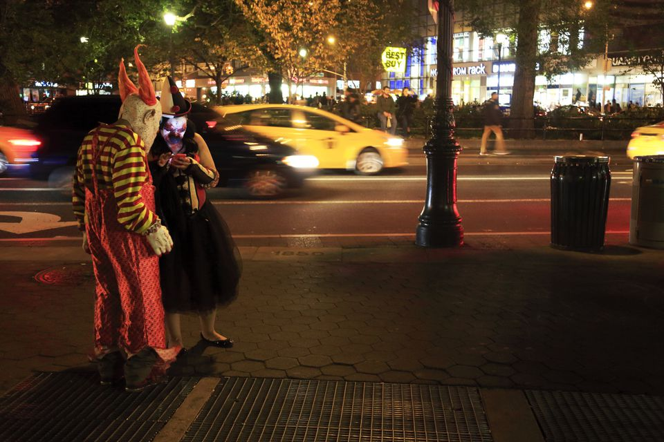 People in Halloween costumes checking on their cellphone in Union Square