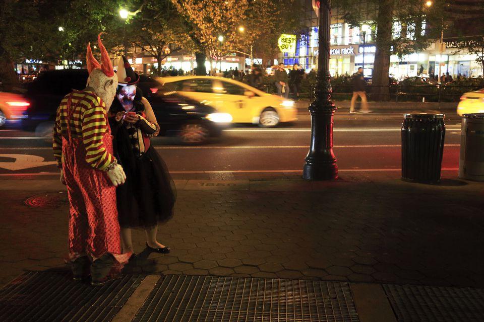 La gente en disfraces de Halloween revisando su teléfono celular en Union Square