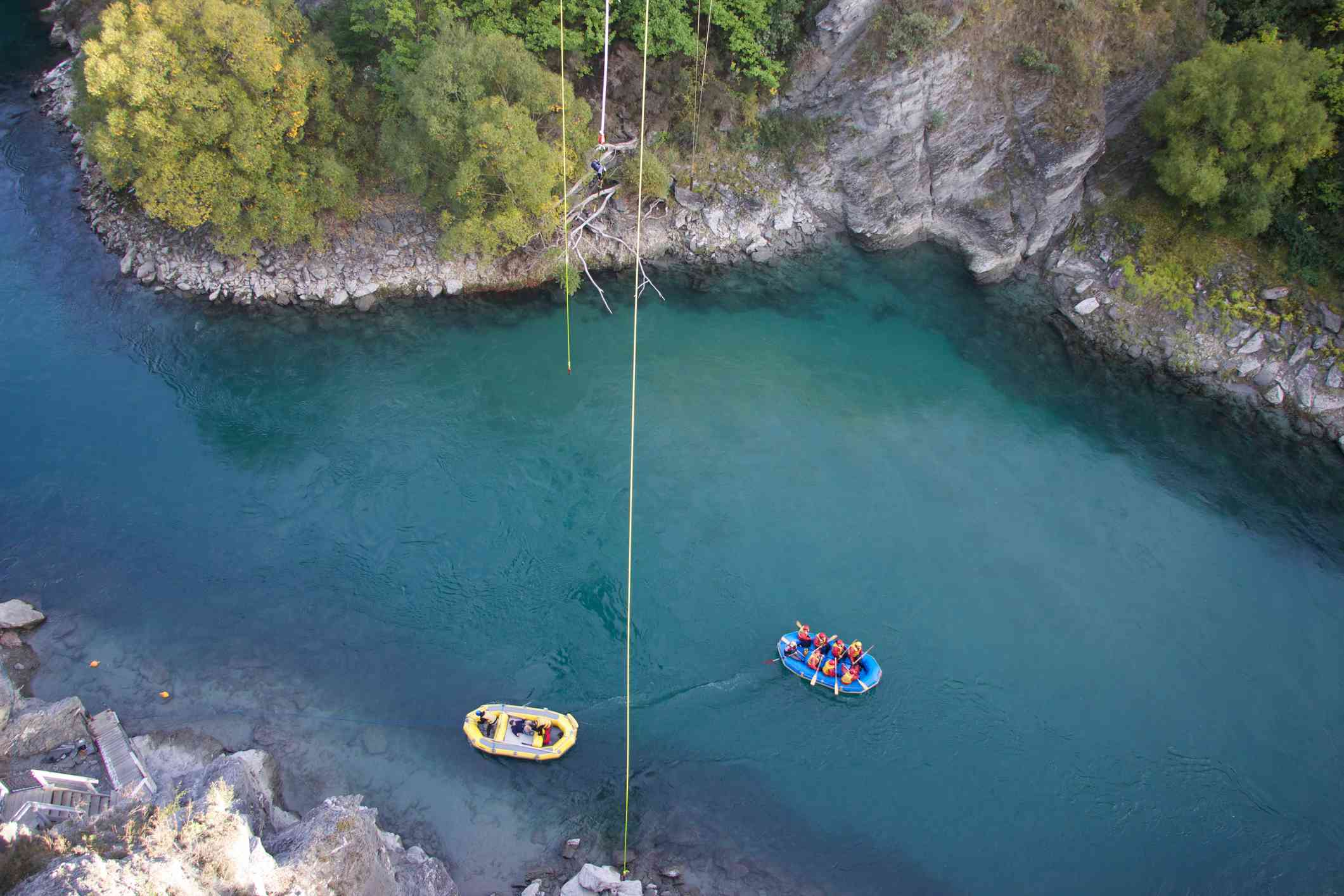 aerial shot of two rafts on a blue river in a canyon