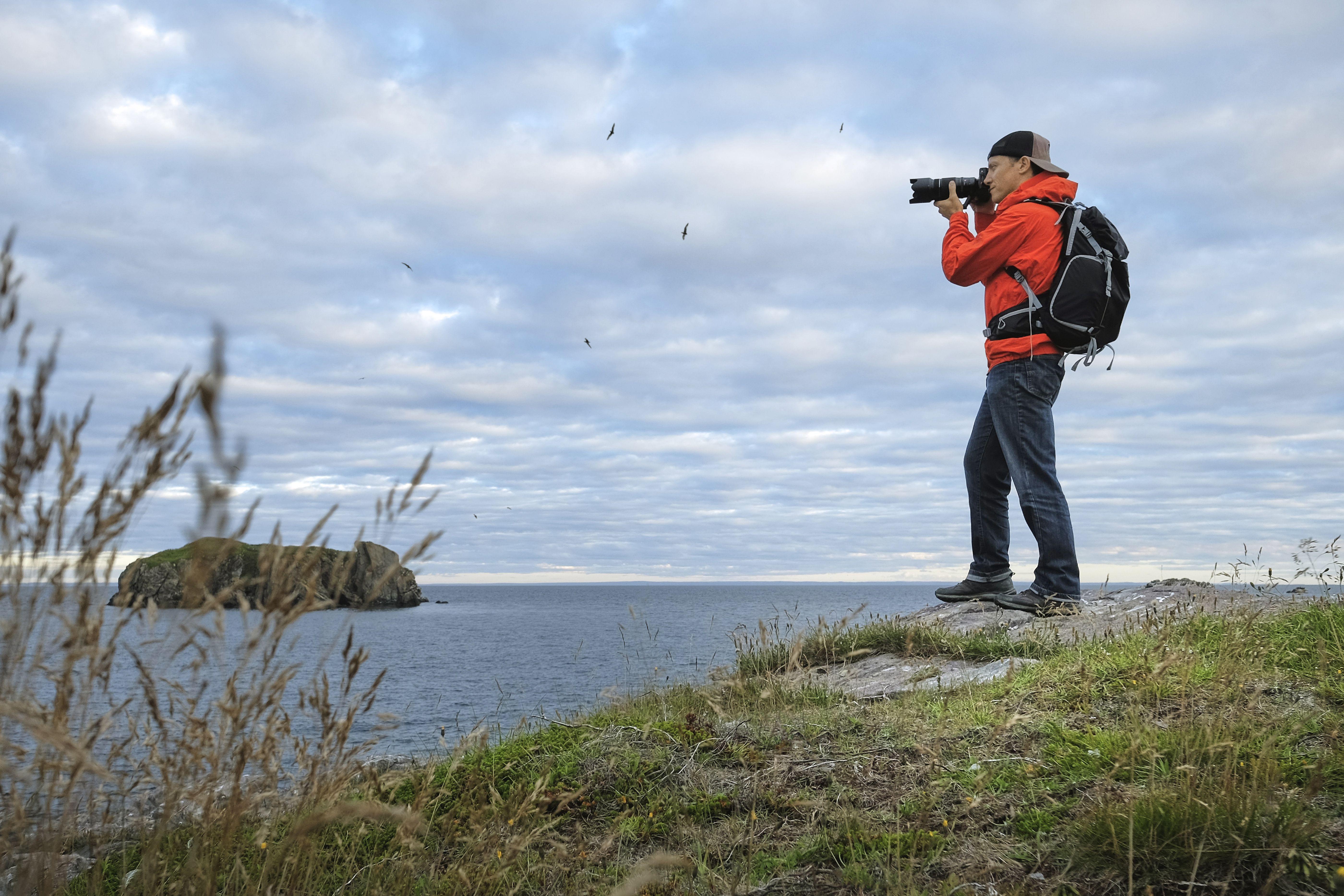 Mid adult man photographing coastline, Saint John, Canada,