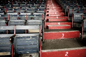 Red painted steps rising between grey stadium seats