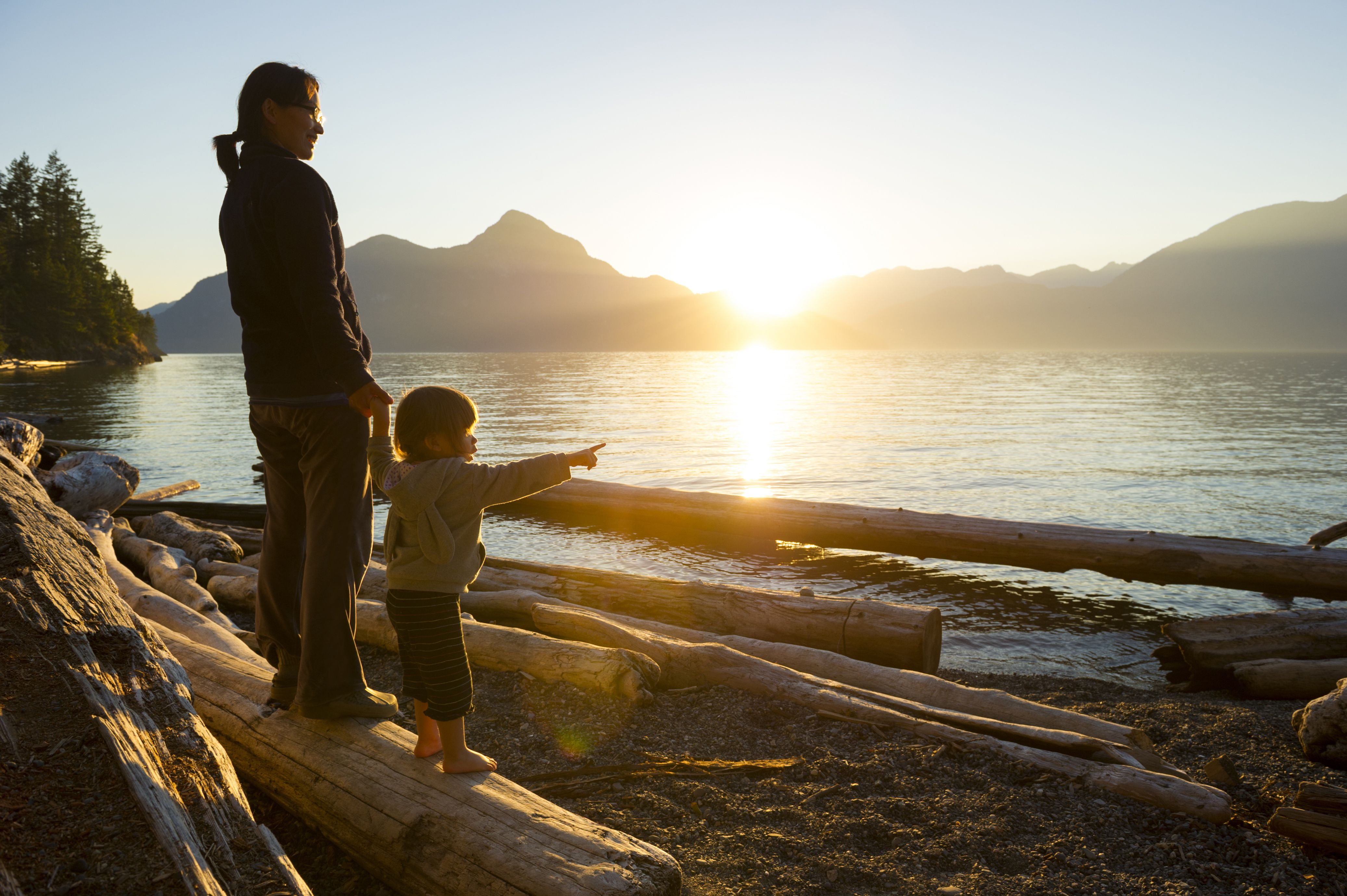 Mother and toddler looking at lake