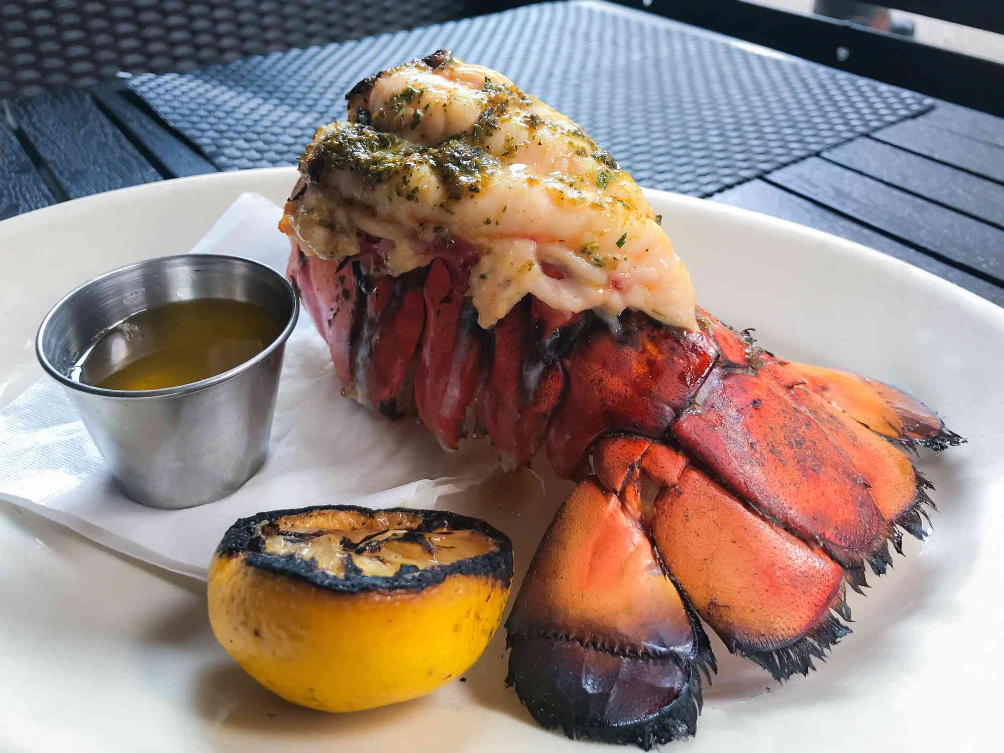 Grilled Lobster Tail on a plate with melted putter and grilled lemon