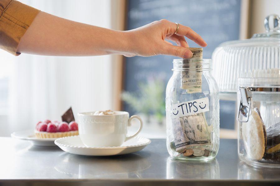 Mujer poniendo dinero en la jarra de propinas