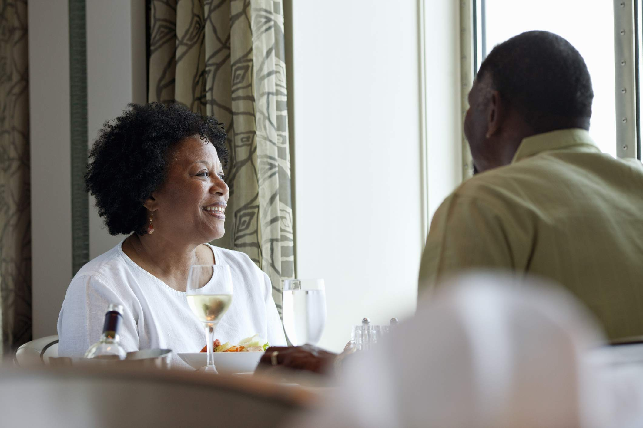 Mature African American woman smiling and looking out the window of cruise ship while eating dinner with her husband.