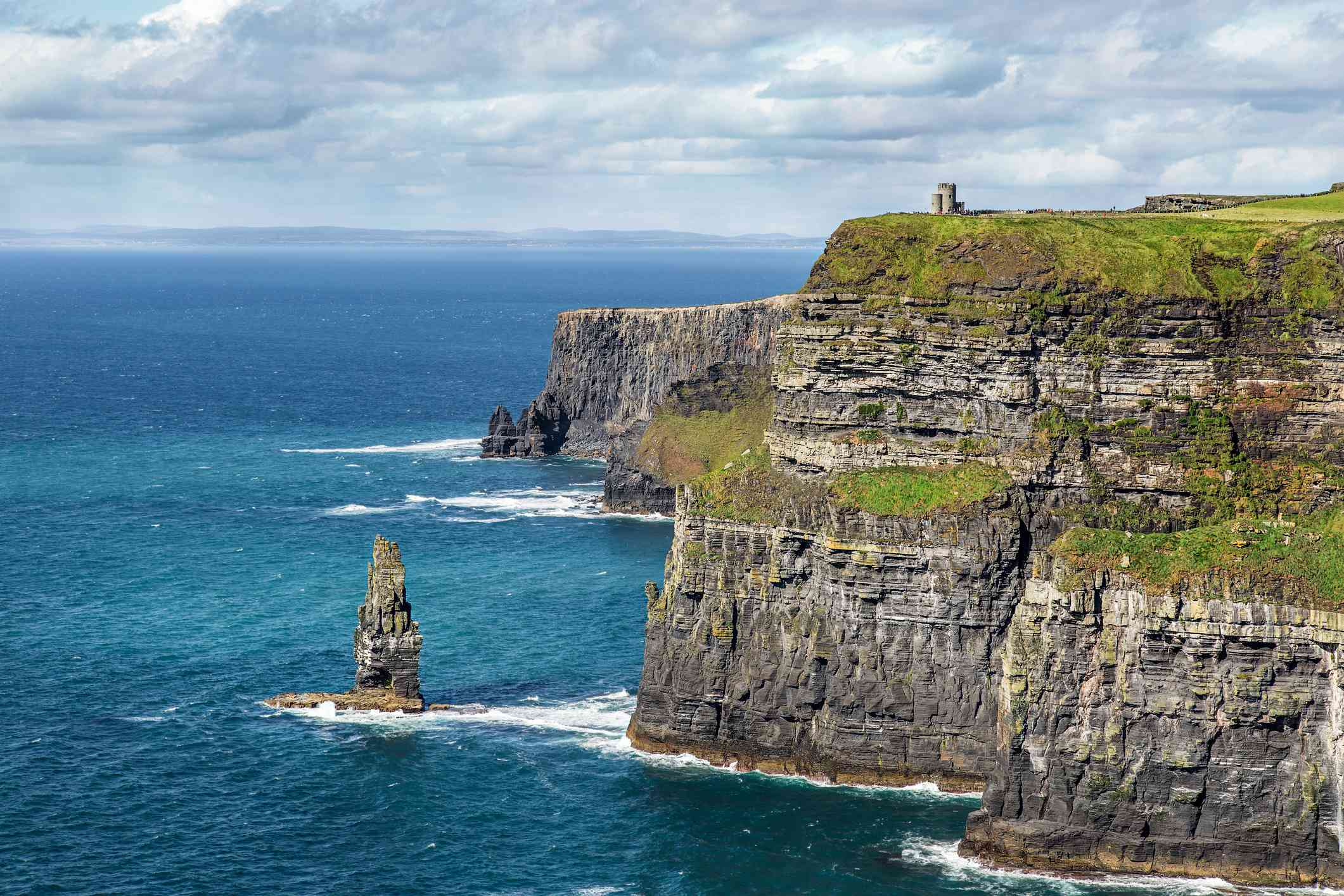 a small tower on the edge of the green and rocky cliffs of Moher overlooking the blue sea