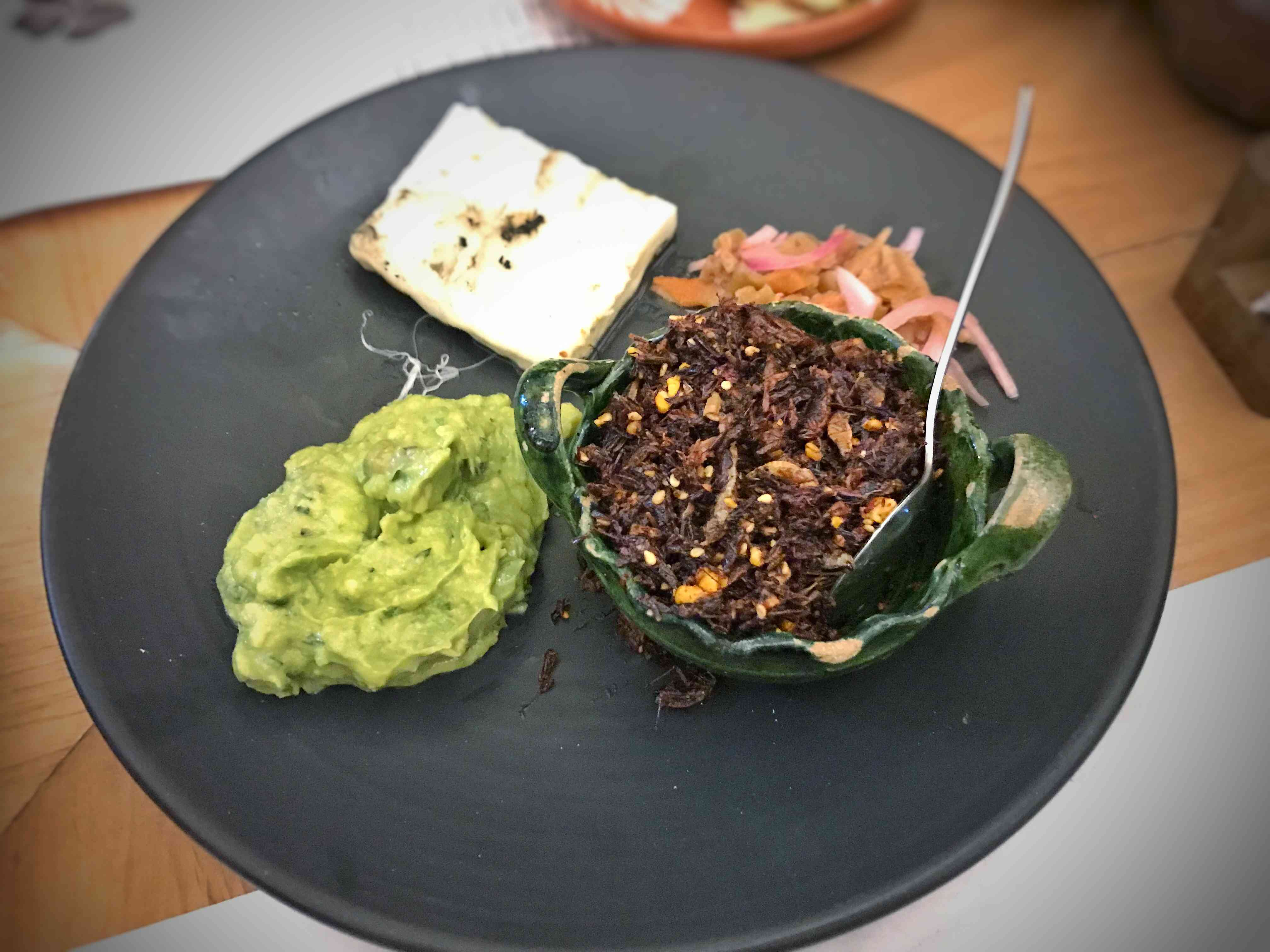 fried grasshoppers with chili flakes in a small green bowl with a spoon. THe bowl is a placte with mashed avocado, queso fresco, and pickled onion from Chapulines in Mexico city