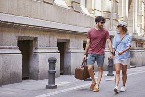 Couple strolling down street with weekender bag