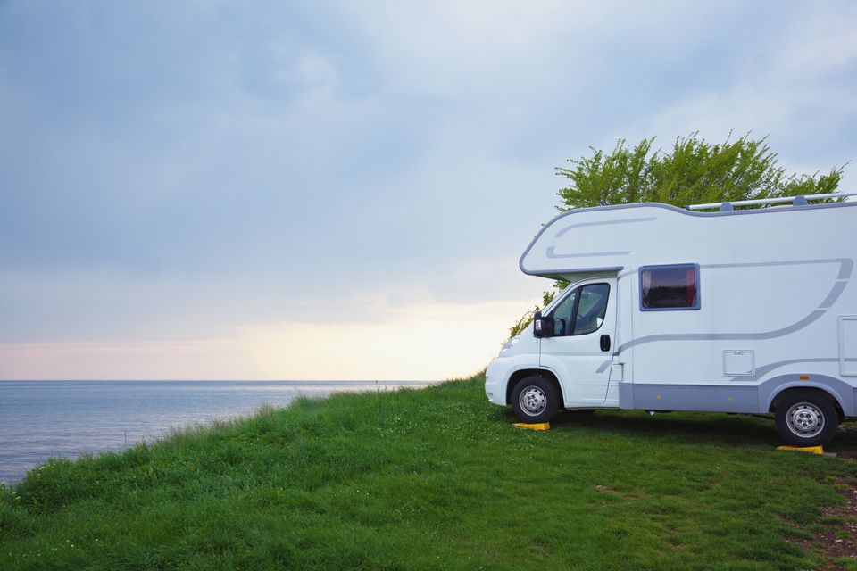 camper parked in grass overlooking the ocean
