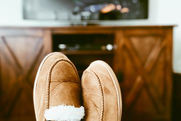 Woman's Slippered Feet on Ottoman in Front of TV