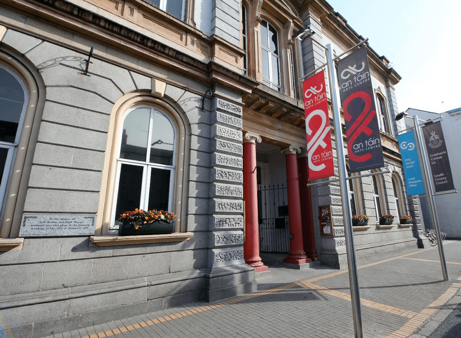 Outside of the An Táin Arts Centre building with street post banner signs advertising the center