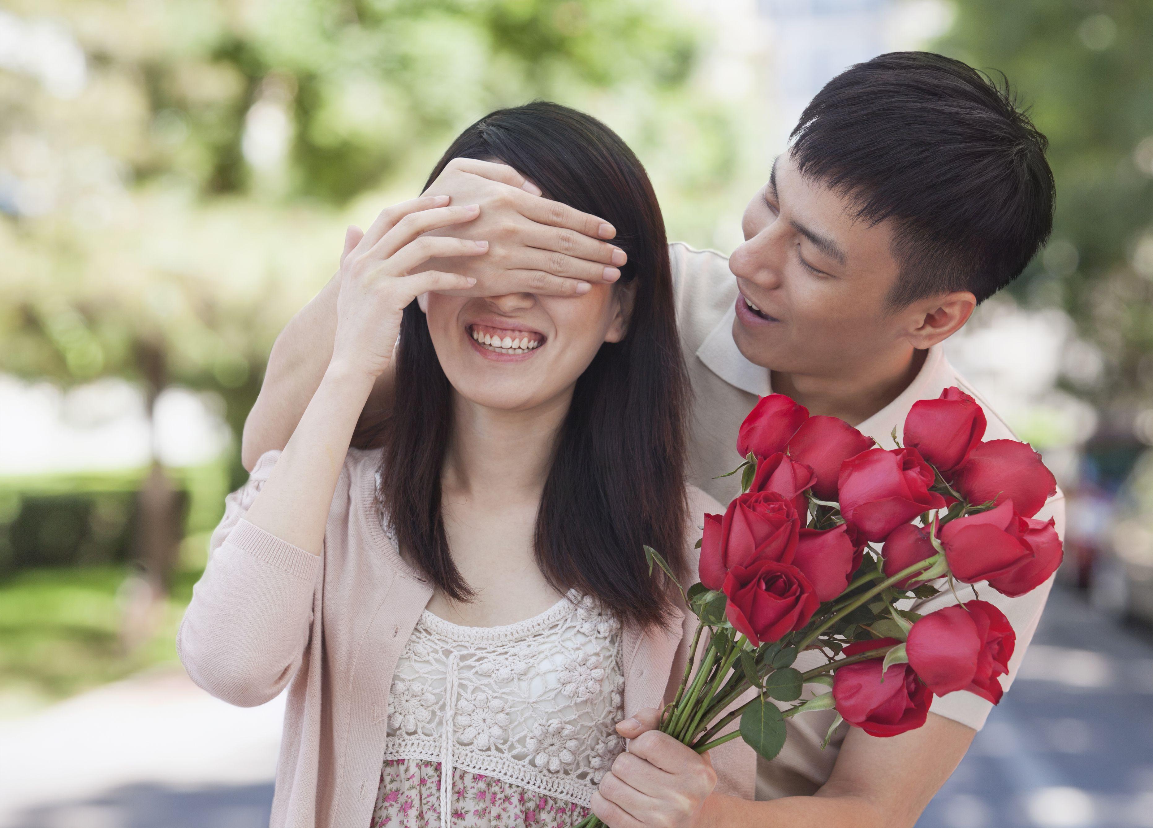Hombre asiático que sorprende a una amiga con un ramo de rosas rojas