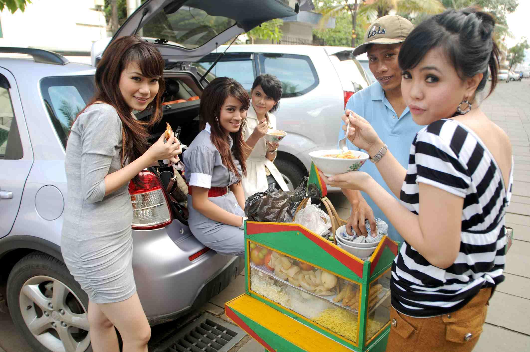 Young women eating at street stall behind Taman Fatahillah (Fatahillah Square).