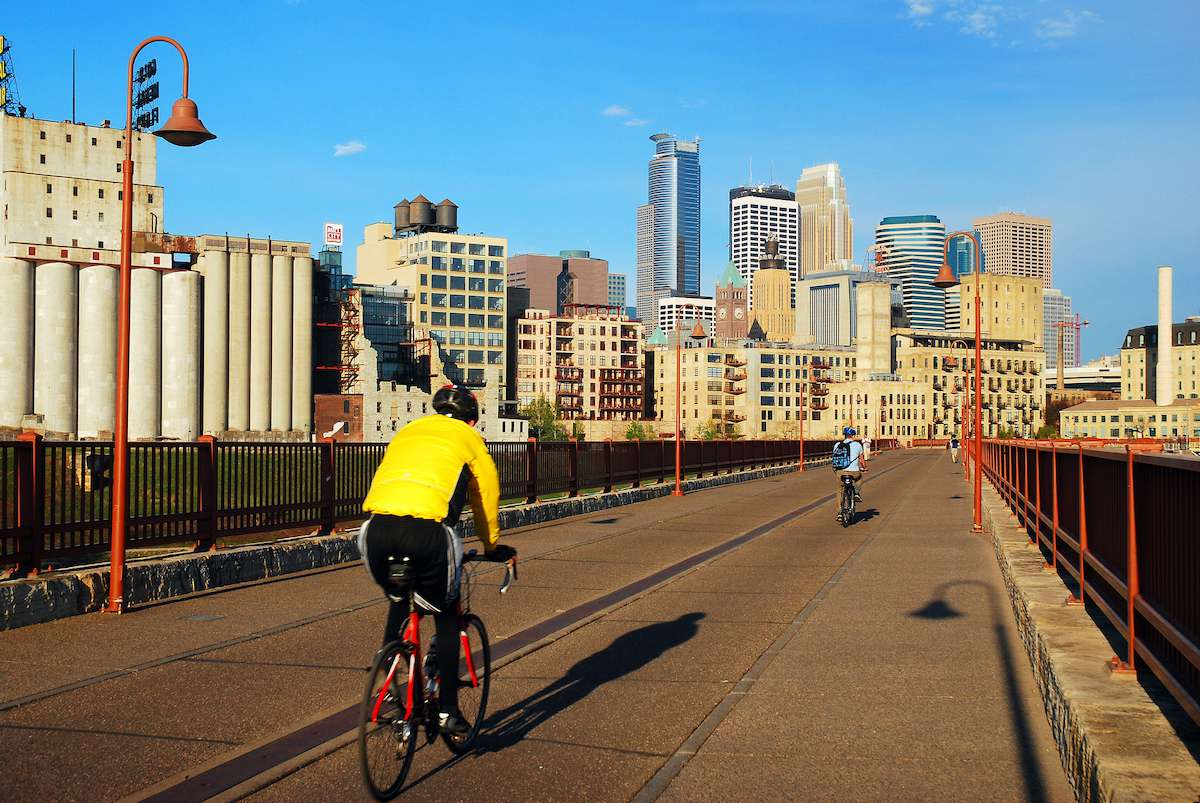 A cyclist rides along a bike path with the Minneapolis skyline in the distance.
