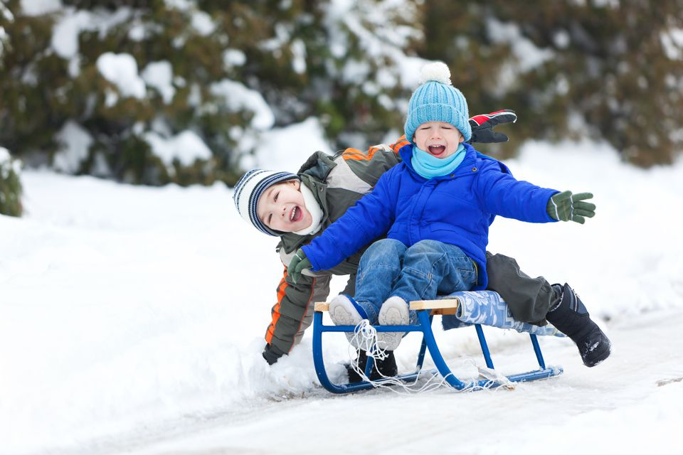 2 boys outside on sled in snow