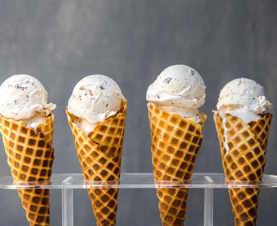 Four ice cream cones with earl grey chocolate chip ice cream in a clear stan
