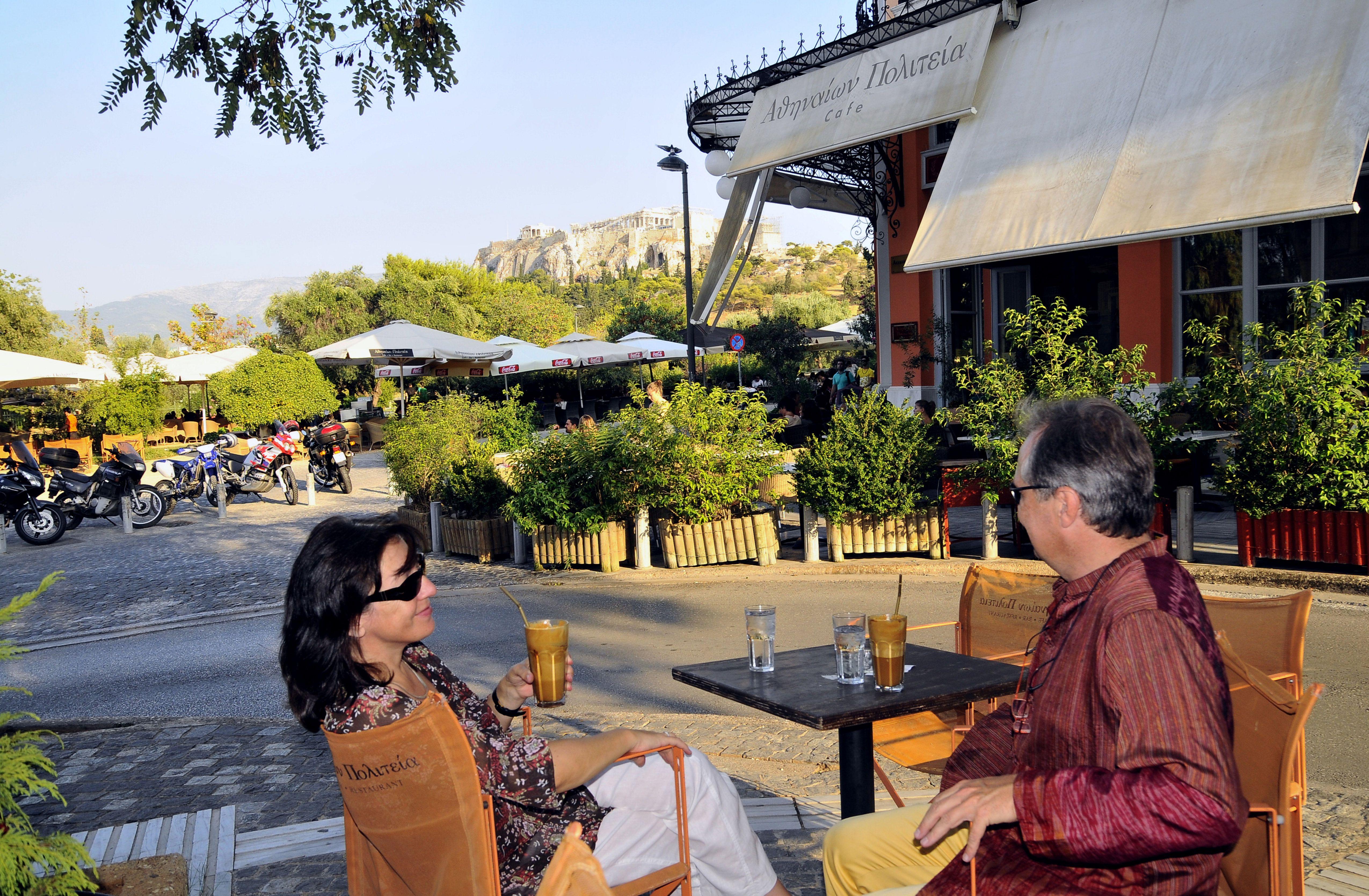 Turistas en un café en la acera del barrio de Thissio, Atenas, Grecia, Europa