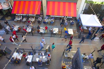 View from above of people moving through and dining at East 4th Street, downtown Cleveland, Ohio, USA. East 4th is a vibrant neighborhood packed with bars, restaurants, entertainment, shops and residential apartments in heart of city. It is often filled with people moving through street, and lined with patios where people eat outside.