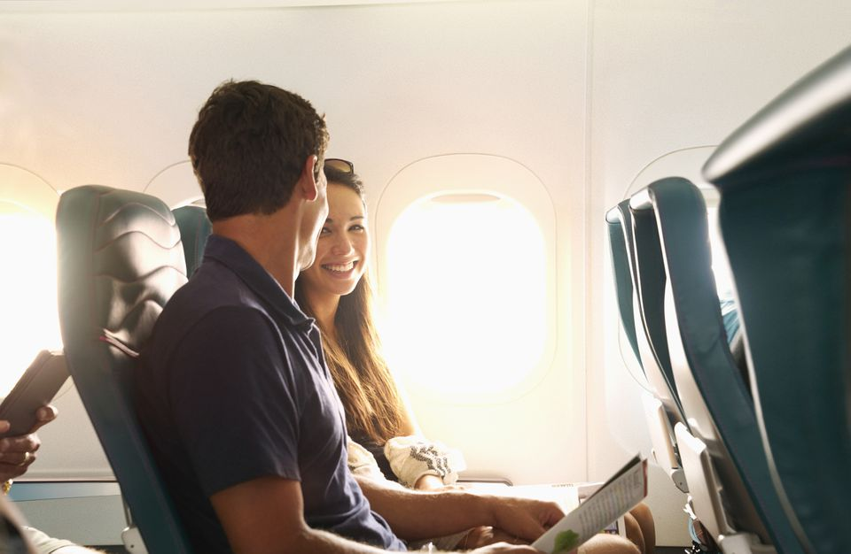 Smiling couple sitting on airplane