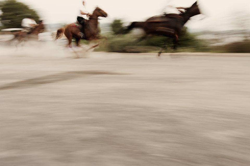 Blurred motion of people riding horses on road, Sedilo, Sardinia, Italy