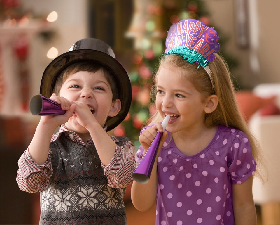 Niño y niña celebrando la víspera de Año Nuevo