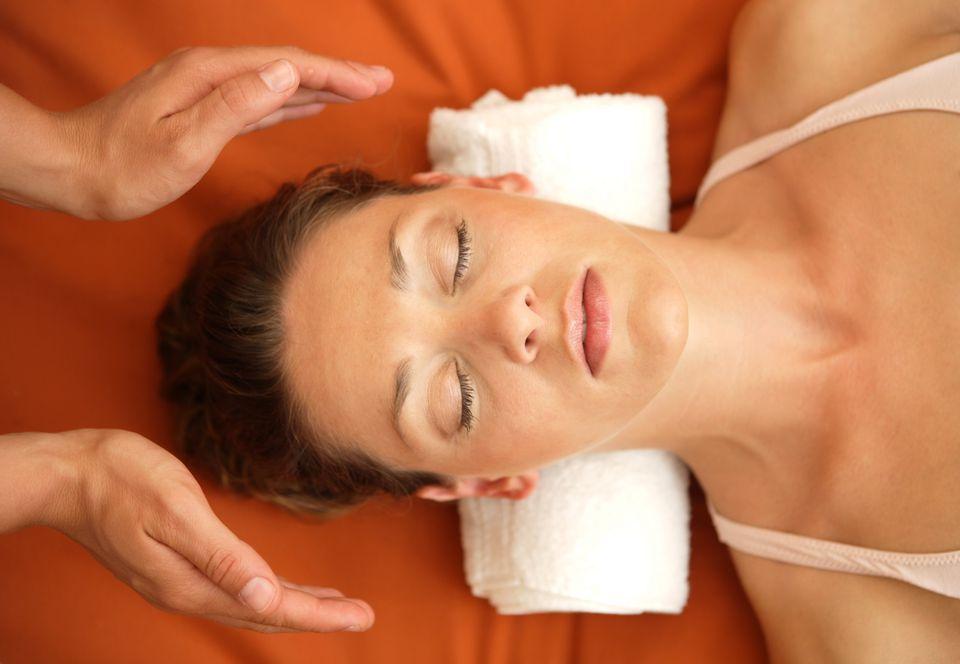 A woman receiving a bodywork treatment like Reiki