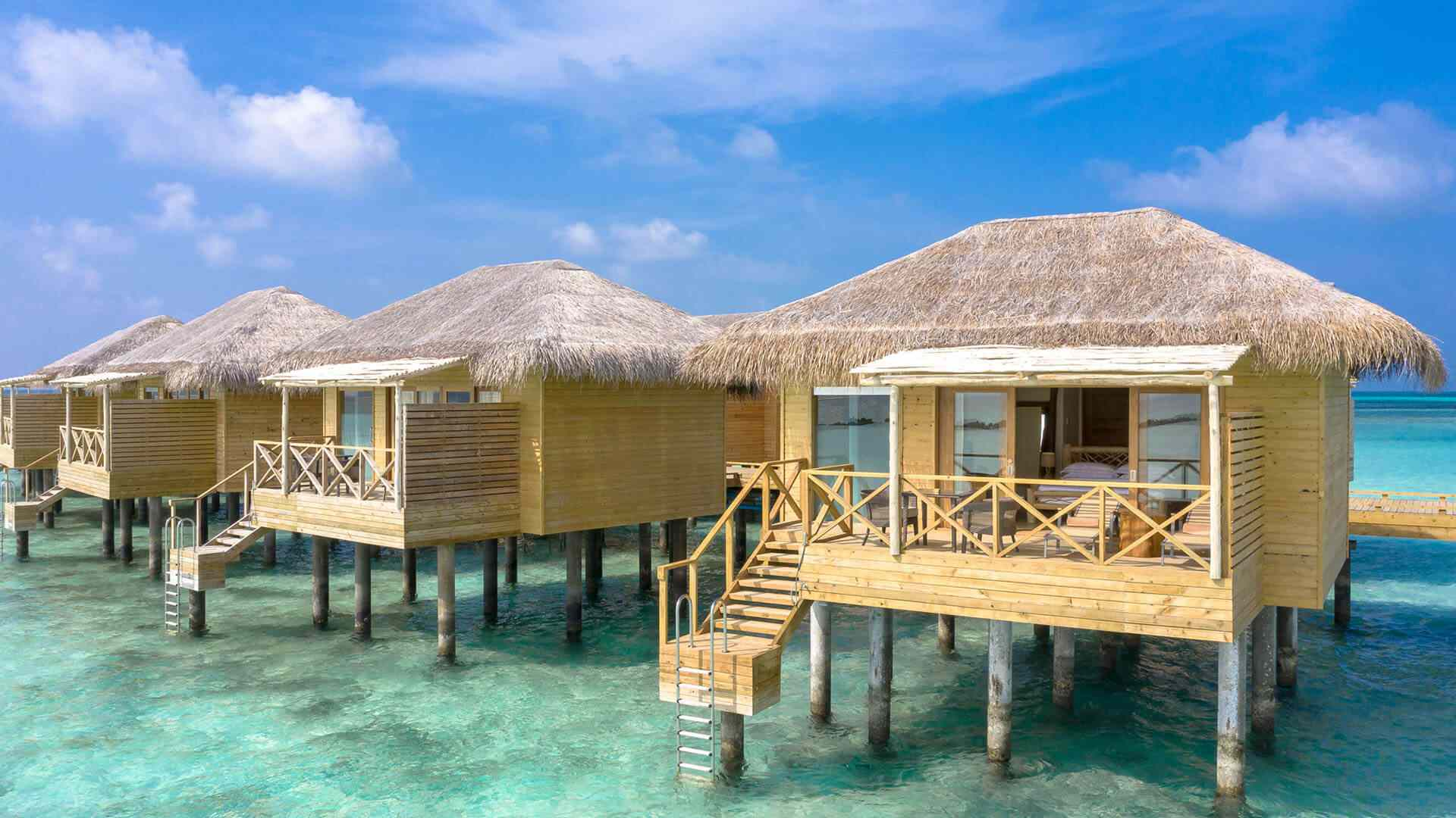 Row of four wooden overwater villas seen from the water