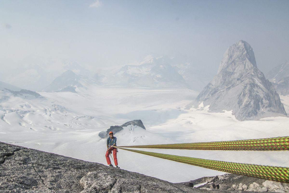 Looking down a rope at a climber with a dramatic backdrop of mountains in the background.