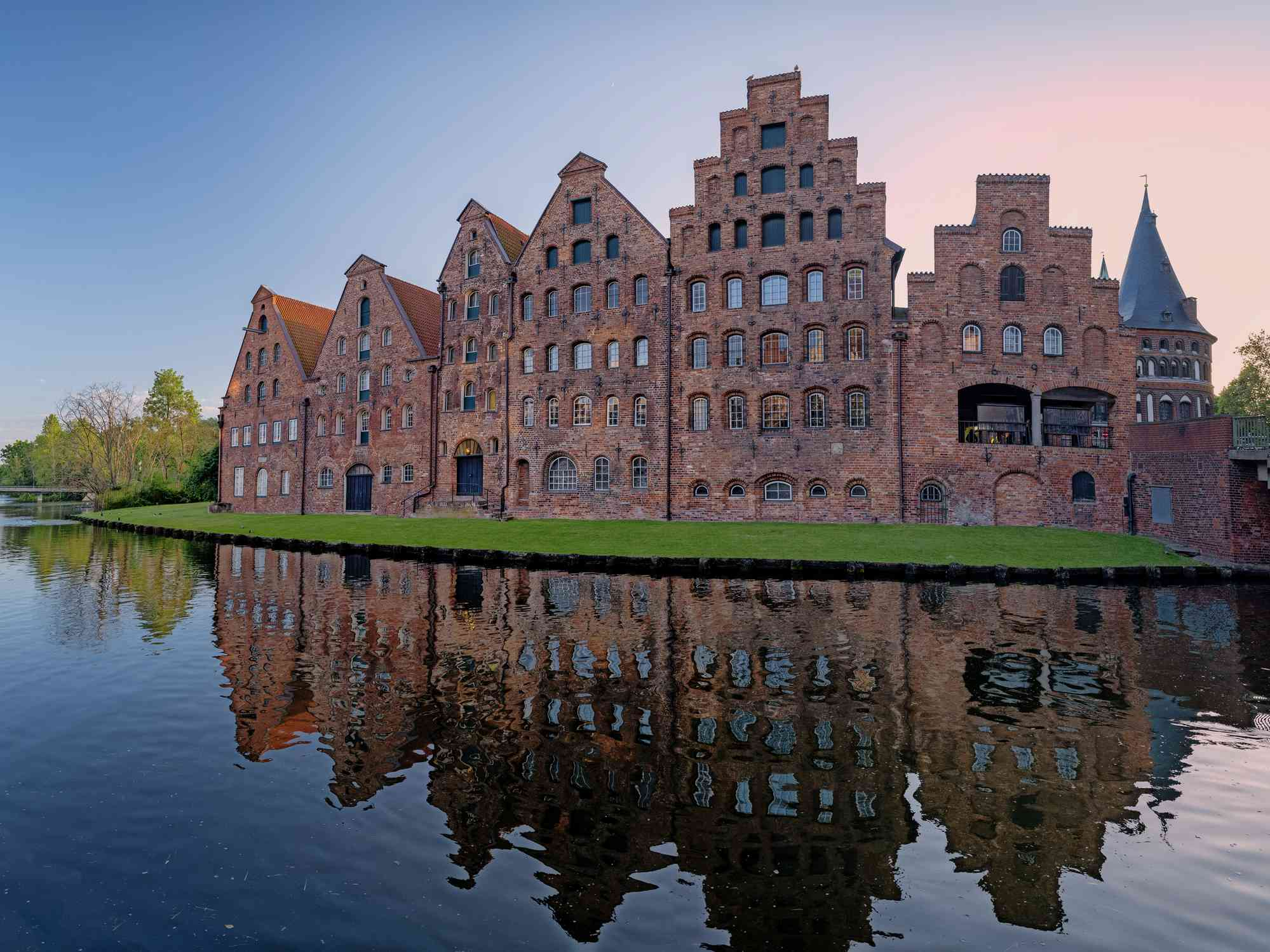 6 narrow brick warehoses of varying heights with pointed roofs on a riverbank