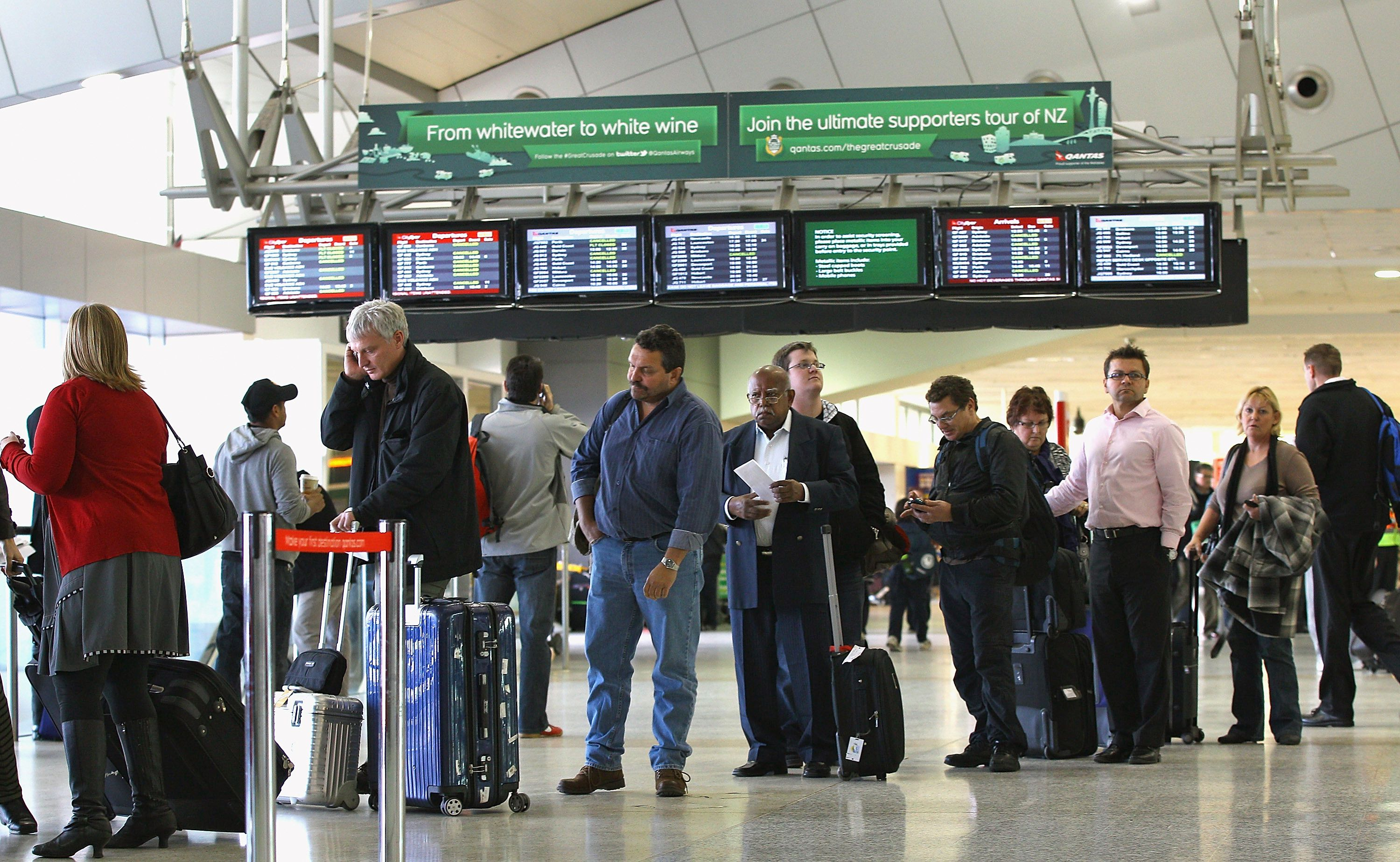 several people waiting in a long line at an airport terminal
