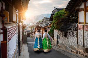 Two women dressed in hanbok dresses in Bukchon Hanok Village, Seoul, South Korea
