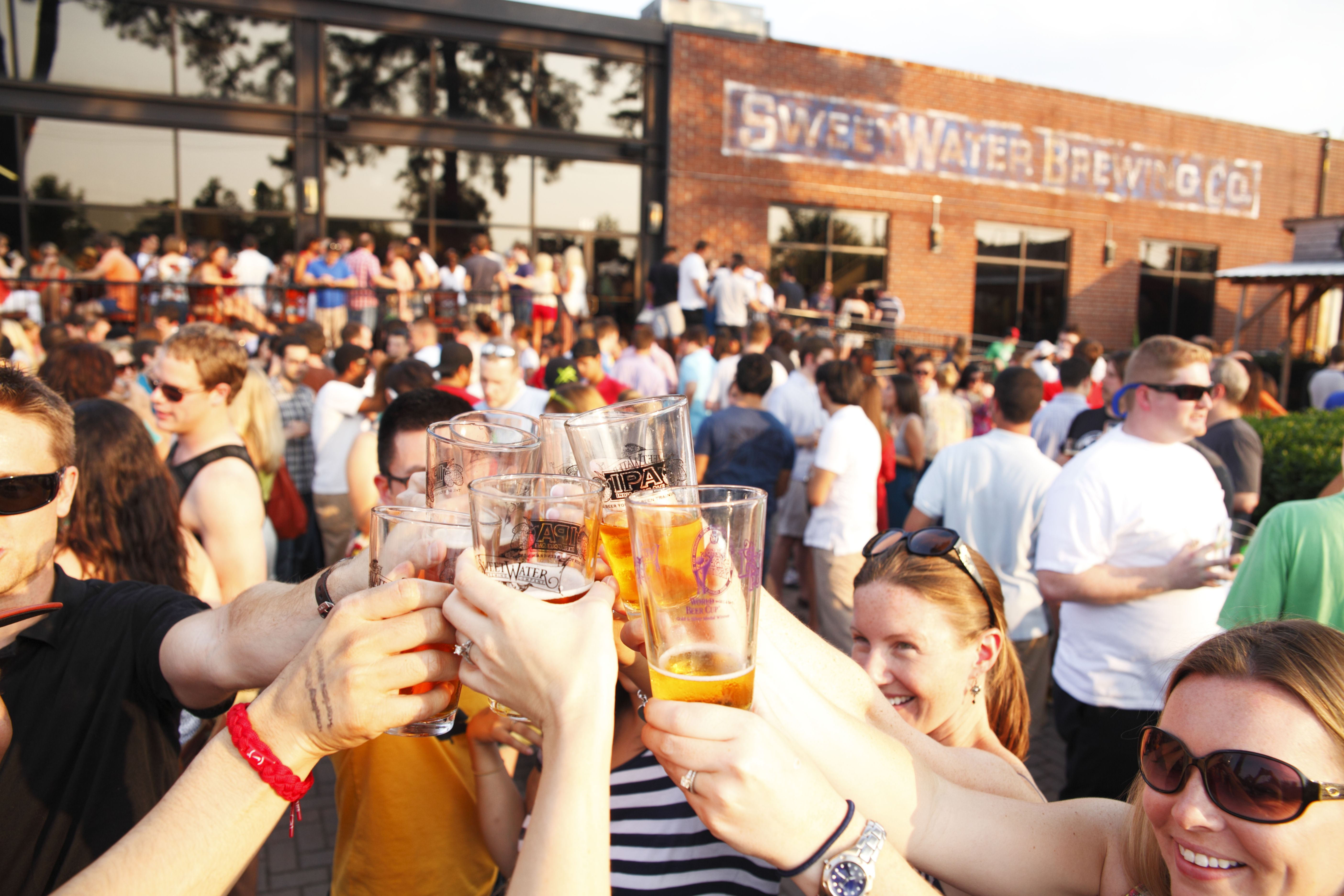 Visitors toast beers outside the SweetWater Brewing Company