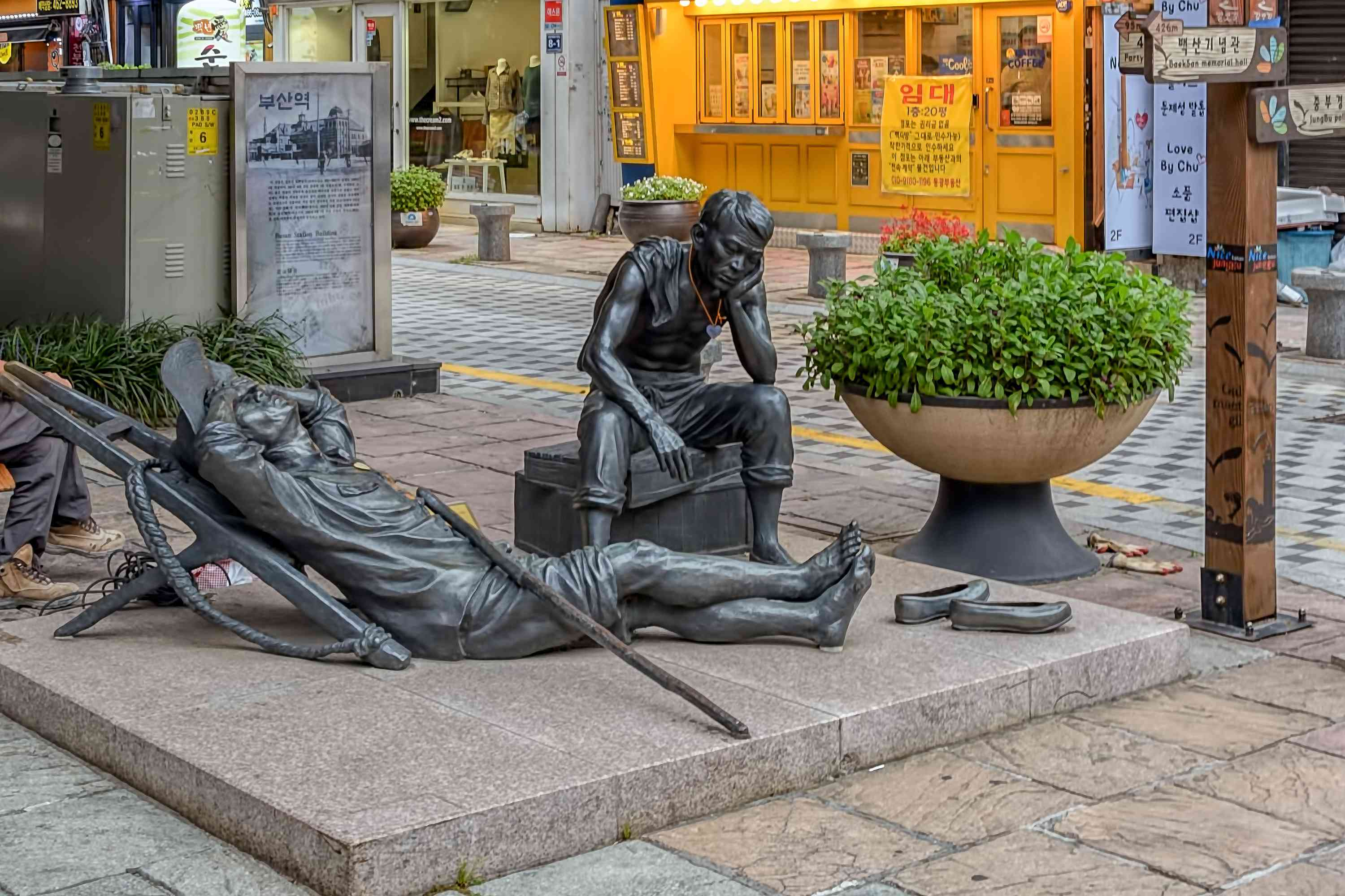 One of the series of brass statues depicting a resting man and his sitting son on the 40 Steps Culture & Tourism Theme Street.