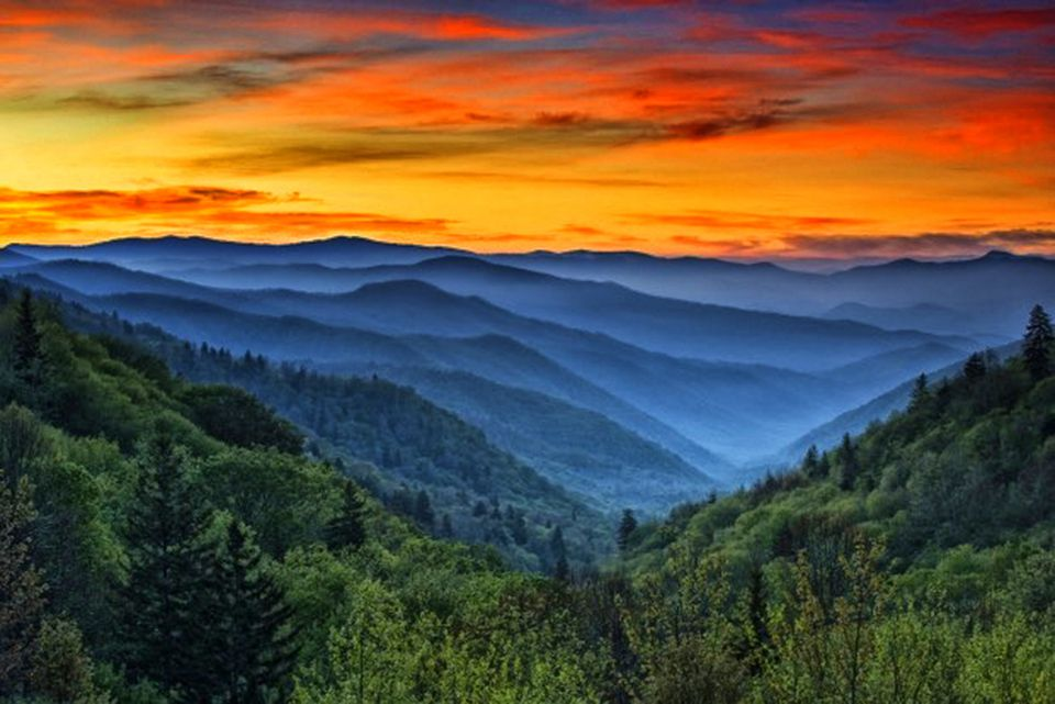 Sunset over a series of misty ridges and mountaintops