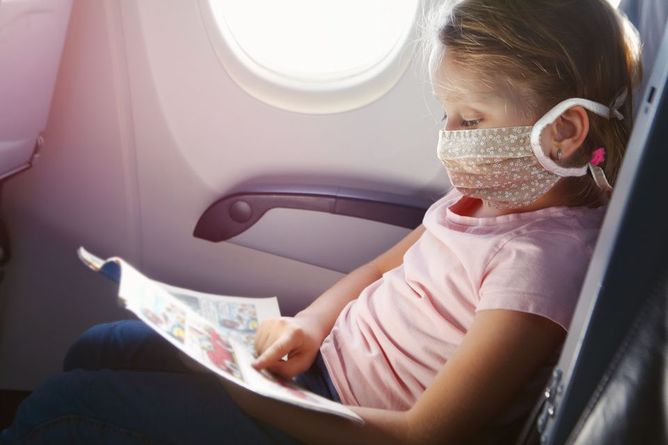 Girl with face mask flying by airplane