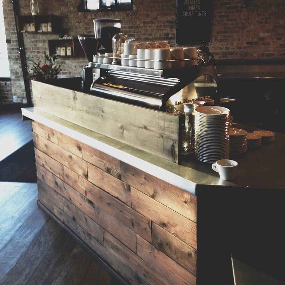 Espresso machine on a wood-paneled counter with coffee cups and saucers