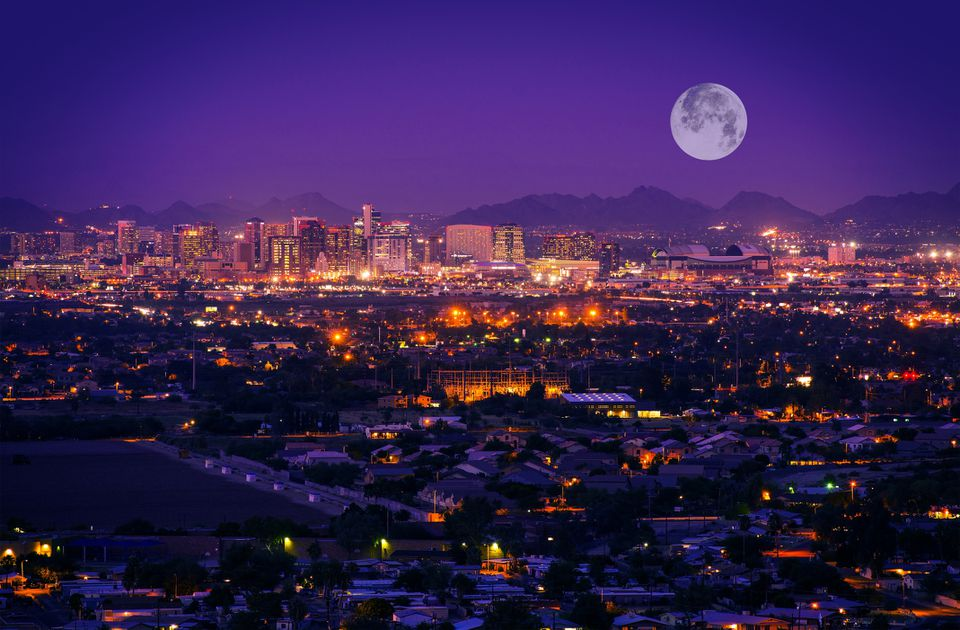 View of CityScape, Phoenix, AZ lit up at night from above with the moon hanging large just above the mountains on the horizon