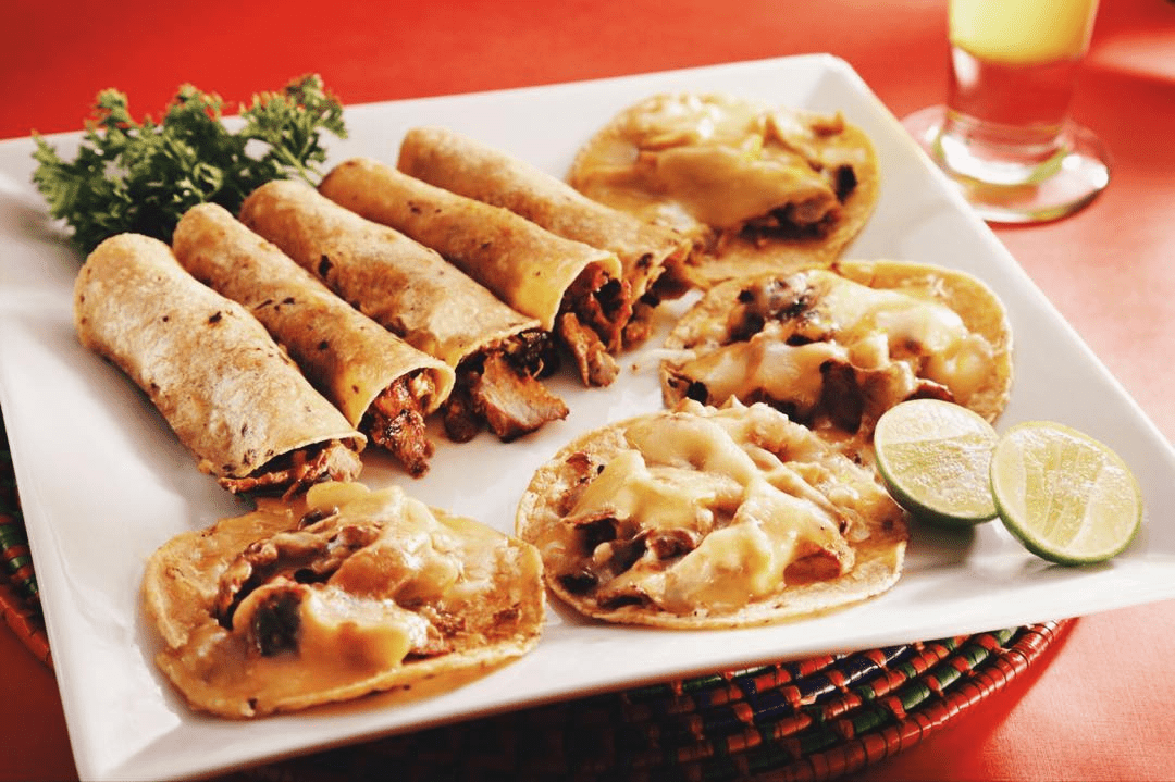 Tacos al pastor on a plate with lime and cilatro. Some of the tacos have cheese on them