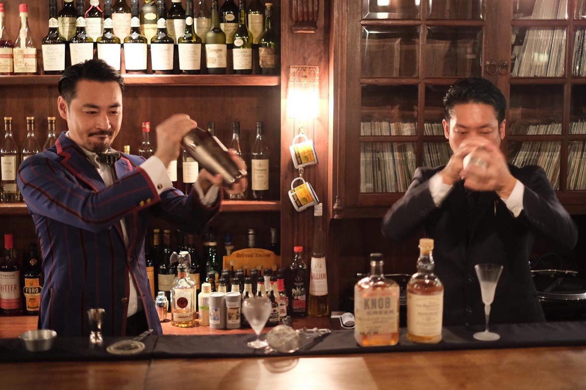 Two bartenders shaking drinks
