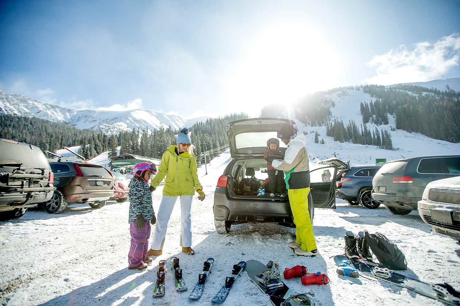 Family at a parking lot unloading ski and snowboard equipment out of their car