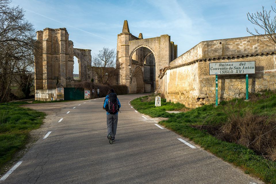 Woman hiking past Old Monastery of San Anton, Camino de Santiago, Spain.