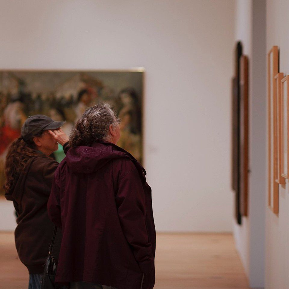Two patrons looking at art in the Dennos Museum Center in Traverse City, Michigan
